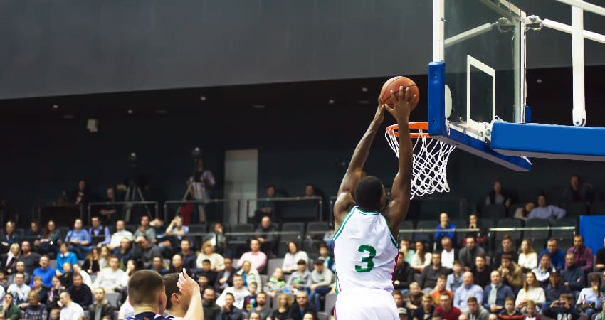 A basketball player lands a lay-up in a packed stadium