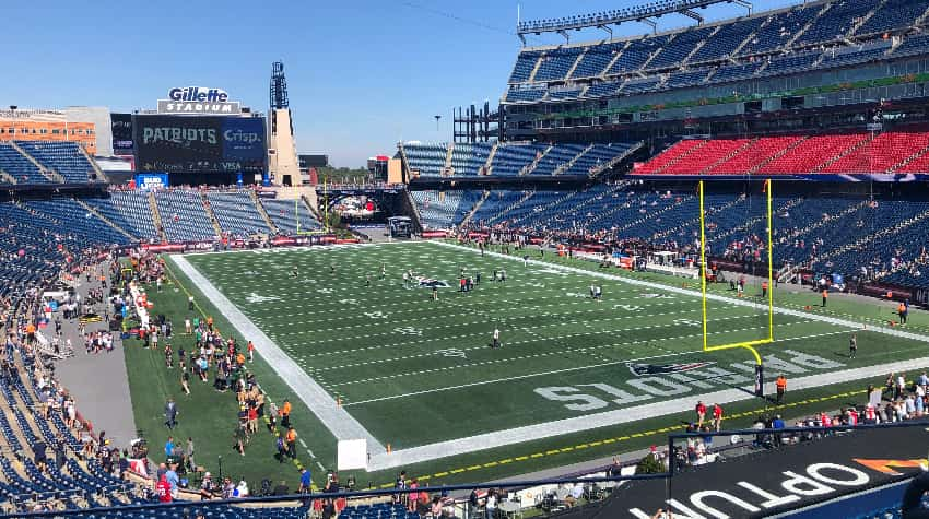 Gillette Stadium on a sunny day, fans and players walking around on the field