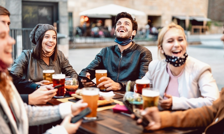 A group of four people laughing, talking and drinking beer