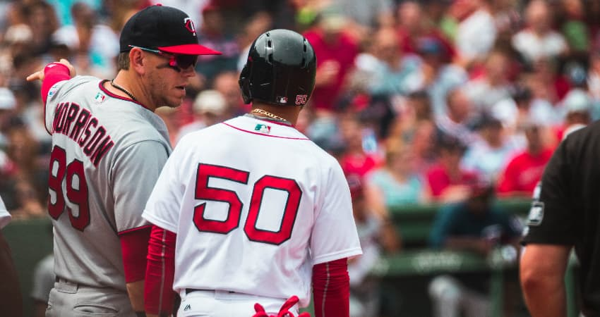 Two baseball player talk on the field, fans filling the seats of Fenway Park in Boston