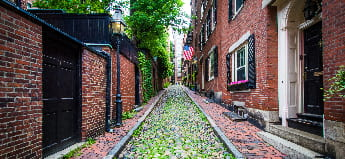 A mossy cobblestone street lined with red-brick houses in Beacon Hill, Boston