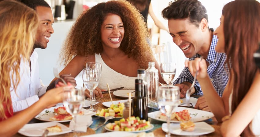 A group of friends eat and laugh in a bright restaurant