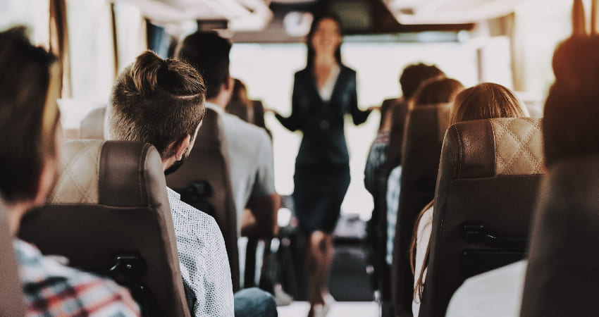 A tour guide talks to a charter bus full of passengers