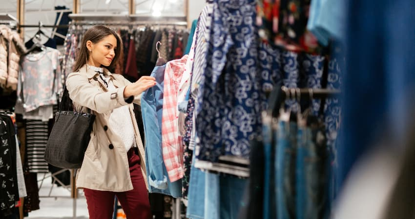 A woman looks through a rack of clothes in a clothing store