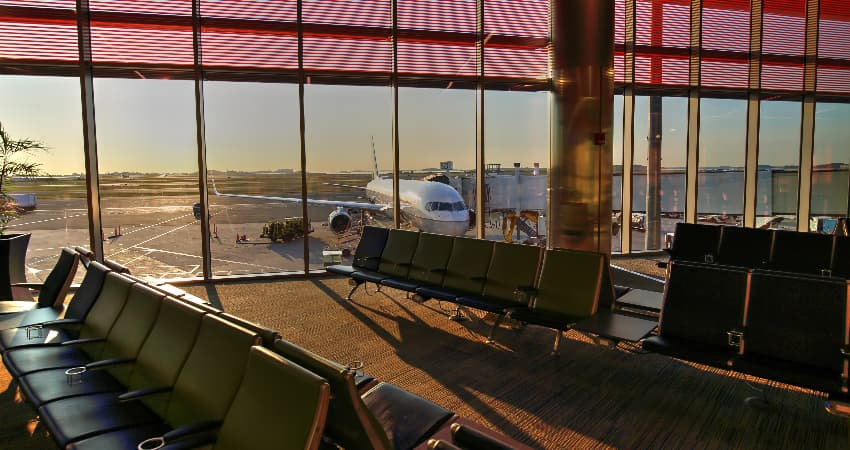 The sun rises over an empty gate at Boston Logan International Airport, a passenger plane visible outside the floor-to-ceiling windows